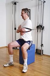 Sittande kroppsvridning fram som stabiliserande övning av nedre ryggen, och mobiliserande i bröstryggen. # serier a 30 repetittioner på varje sida med 6kg i drag apparat. En av 8-11 övningar för en patient med ryggsmärta.