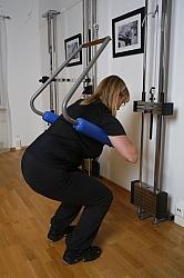 För att klara ett högt antal repetitioner avlastas något av kroppsvikten vid att avlastningsbygeln är festat til et vertikaldrag. Därmed kan patienten genomföra en funktionell knäböjning och sträck i en funktionell viktbärande utgångsställning med normal muskel aktivitet i båda benen.